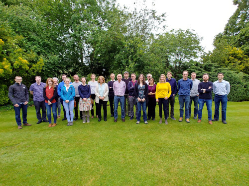 A photo of the 23 employees of Quintessa at the 2019 away days, standing on a lawn as a group, smiling at the camera.